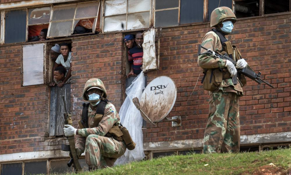 South African National Defense Forces patrol the Men's Hostel in the densely populated Alexandra township east of Johannesburg, Saturday, March 28, 2020, enforcing a strict lockdown in an effort to control the spread of the coronavirus.