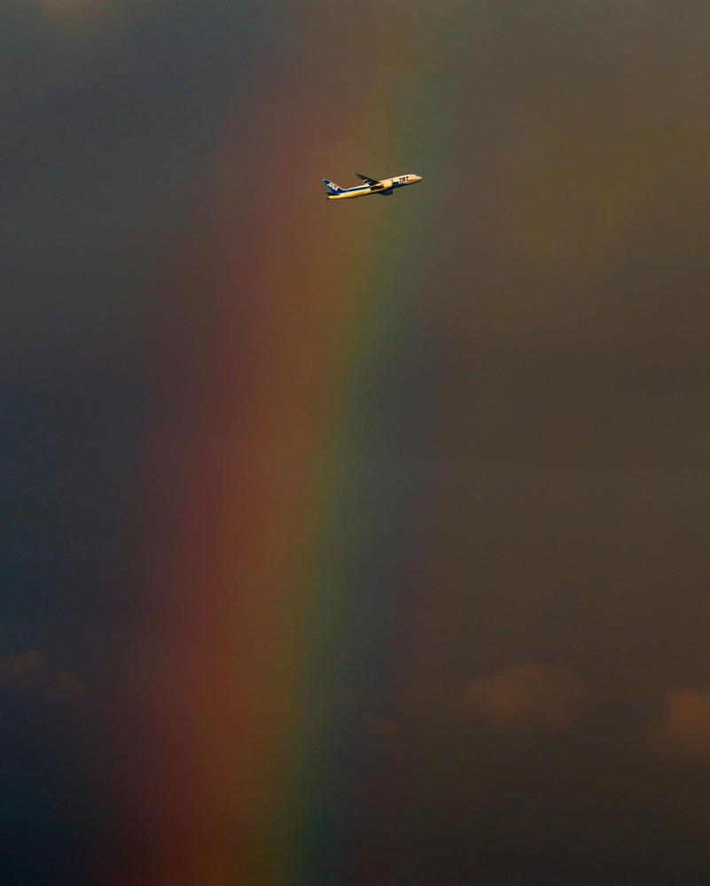 A passenger plane flies in front of a rainbow during New Year's Eve celebrations in Taipei, Taiwan