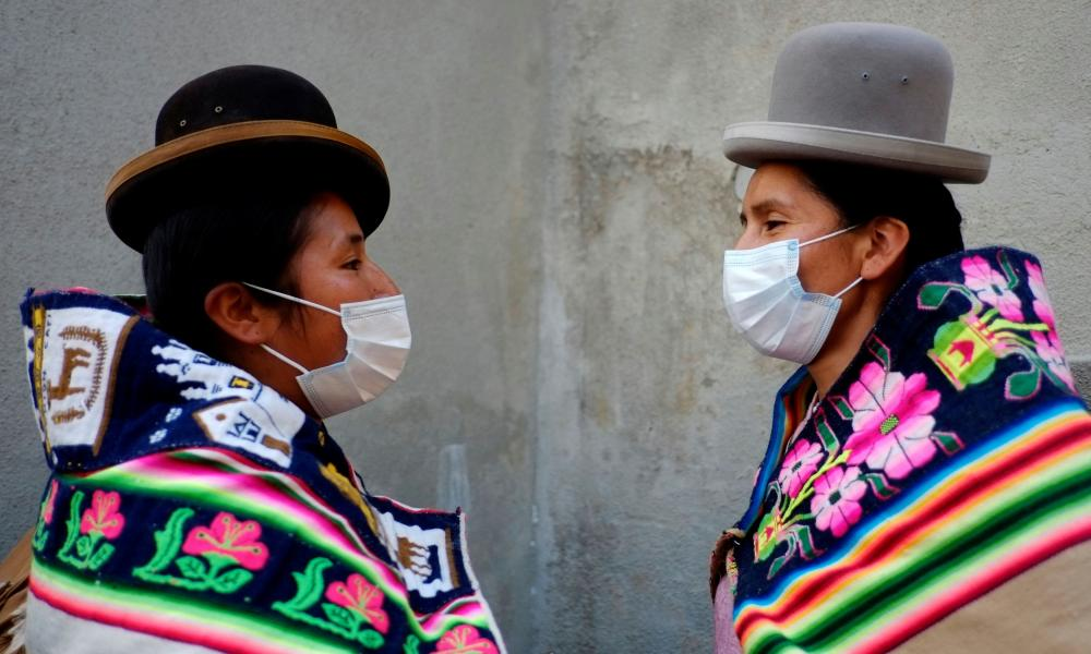 Aymara women from Huachacalla wearing face masks wait for a meeting at the La Casa Grande del Pueblo after the election day in La Paz.
