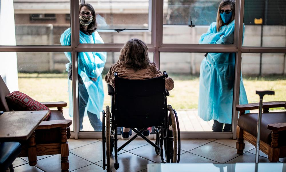 Relatives chat through a window to a resident of Casa Serena, a home for elderly people, in Johannesburg