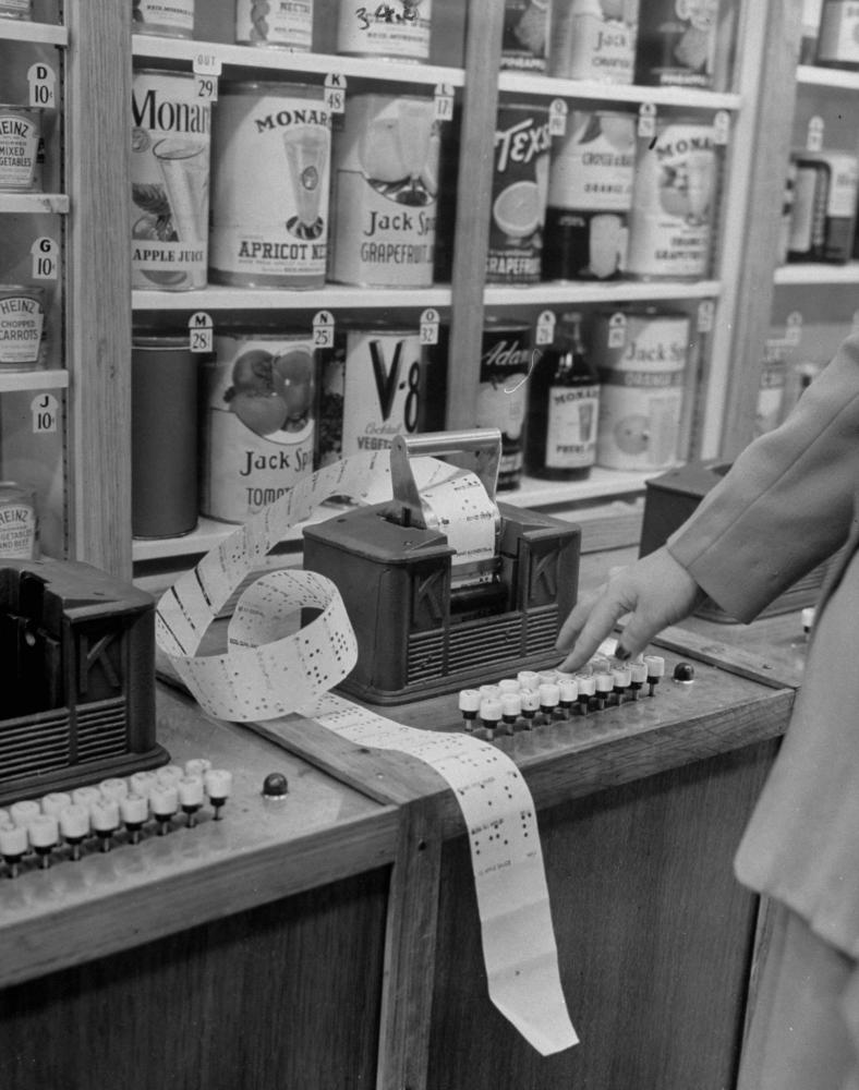 Keedoozle automatic grocery store with a customer using the key to select products she wishes to purchase.