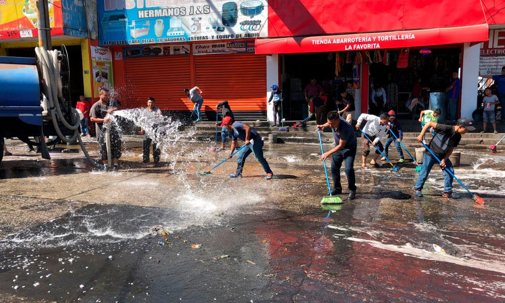 Sellers of La Terminal market disinfect their stalls in Guatemala City, on March 17, 2020. -