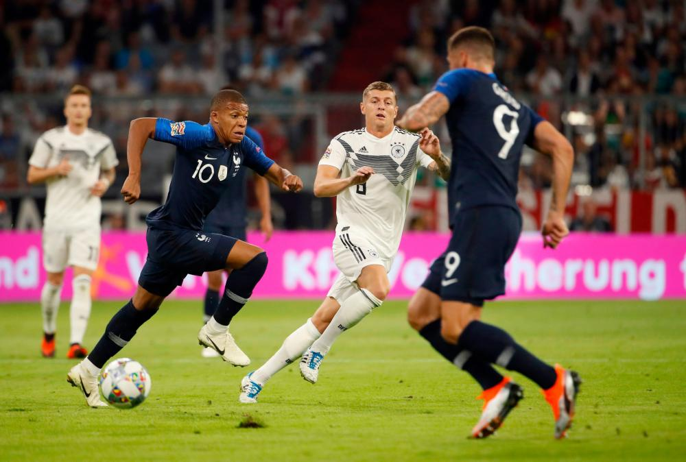 France's Kylian Mbappe and Germany's Toni Kroos vie for the ball.
