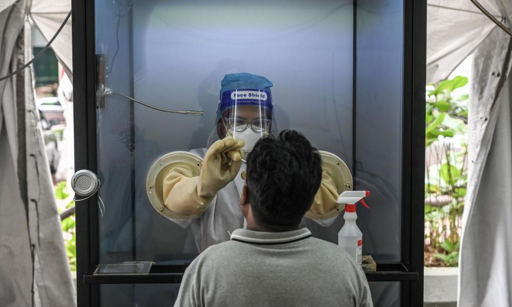 A health worker collecting a swab sample inside a non-contact chamber called the 'Cov-shield' at Sunway medical center in Subang Jaya, on the outskirts of Kuala Lumpur.