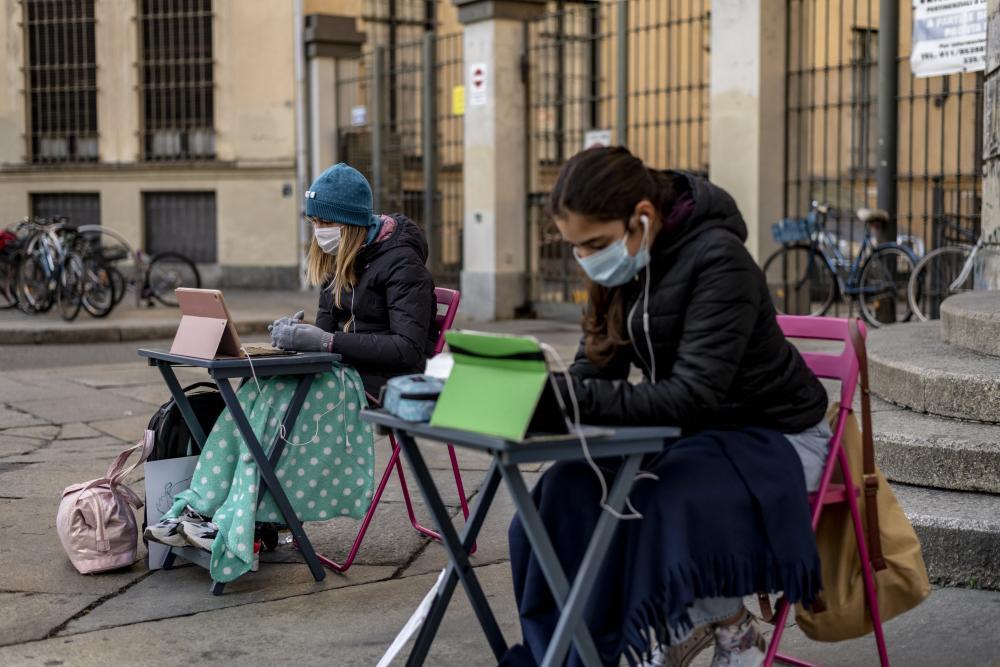 Anita Iacovelli, left, and her friend Lisa Rogliatti, both 12, sit in front of the Italo Calvino school in Turin, Italy.