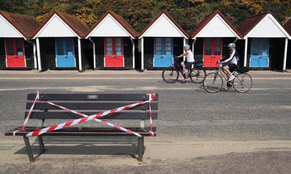 Cyclists making their way past a taped off bench on the sea front on Bournemouth beach on 4 July 2020