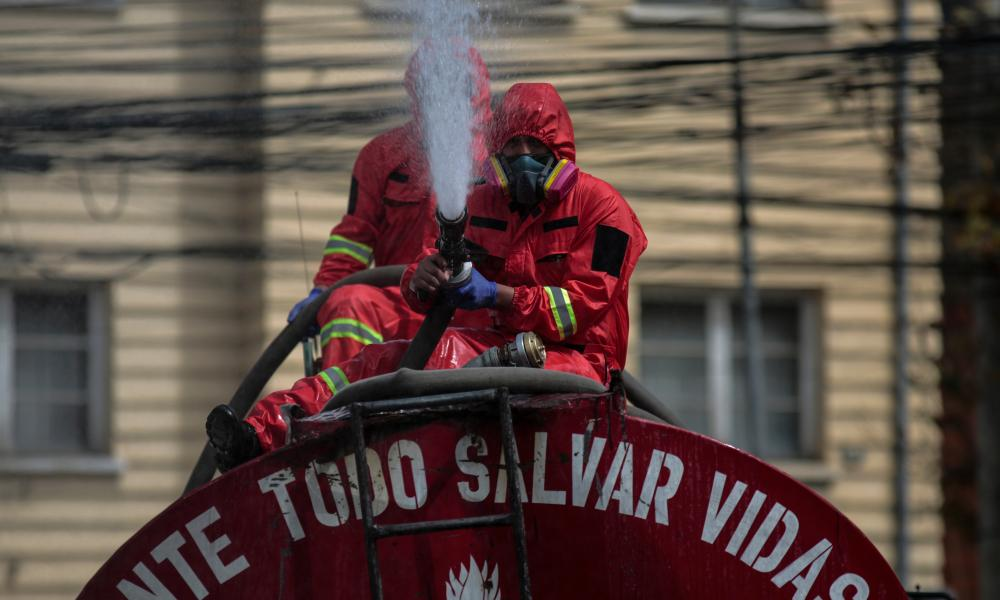 Two firefighters spray water with disinfectant during a disinfection of the streets near a hospital on 23 July 2020 in La Paz, Bolivia.