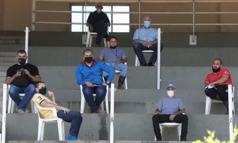 Hostlers and horse coaches wear face masks as they practise physical distancing during a horse race at Beirut Hippodrome