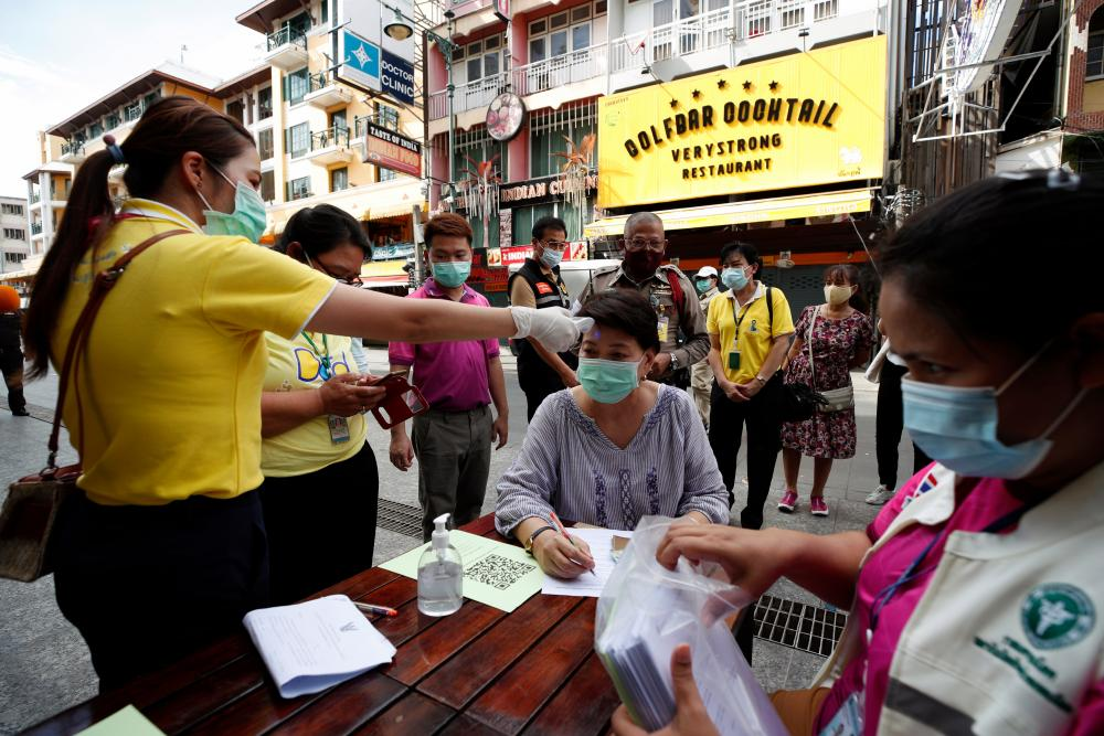 Health officials in Thailand check a woman's temperature during a nasal swab test for coronavirus at a popular tourist spot on Khaosan road in Bangkok