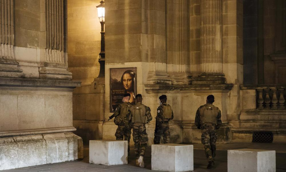 Military patrol near the Louvre museum during curfew in Paris Saturday night. The monthlong curfew came into effect Friday at midnight, and France is deploying 12,000 extra police to enforce it.