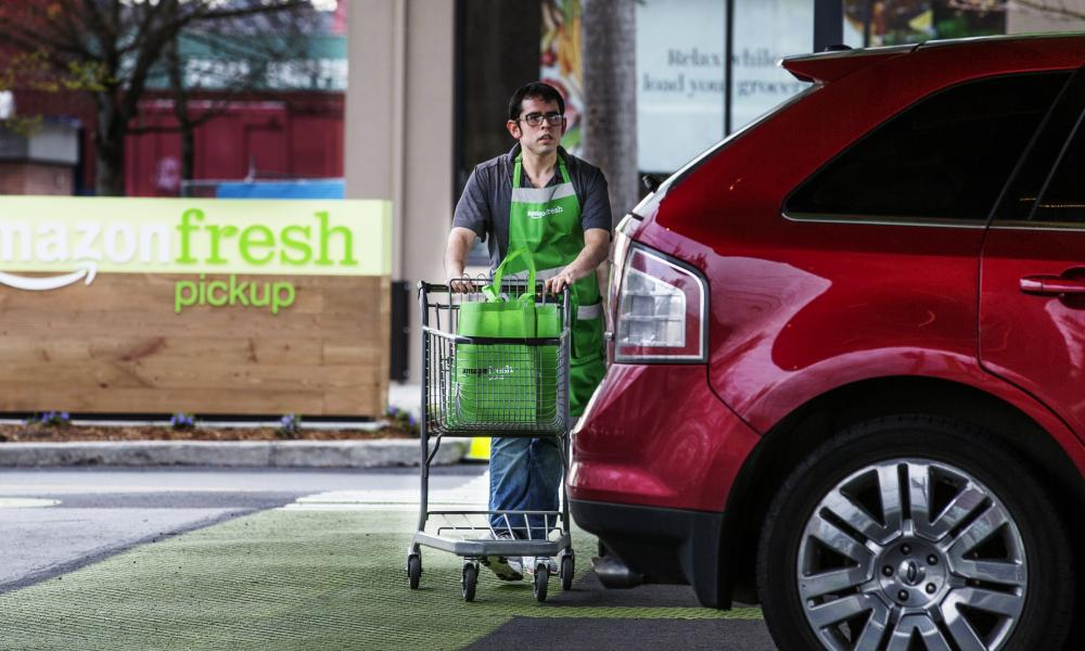 An AmazonFresh Pickup employee wheels grocery bags to a customer vehicle