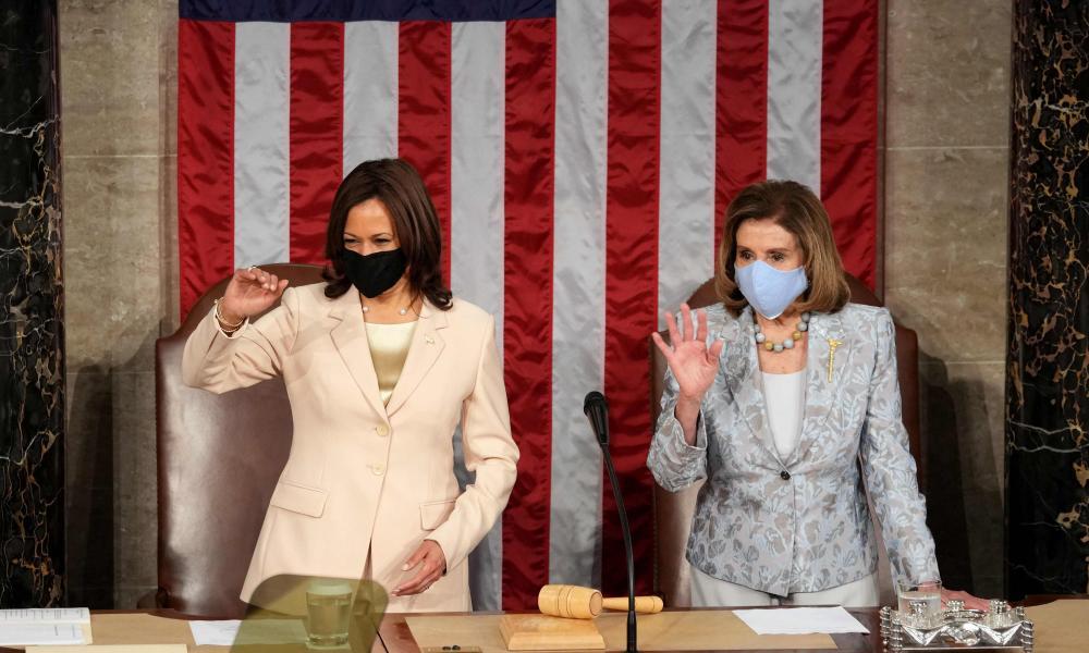 Nancy Pelosi and Kamala Harris wave to colleagues while they wait for Joe Biden to arrive